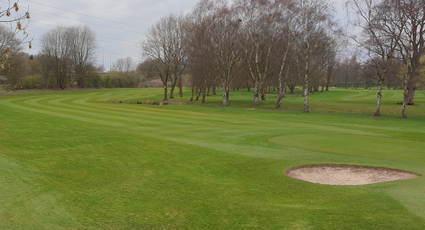 Newly mown fairway with a small bunker